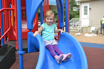 A little girl on a blue sliding board.