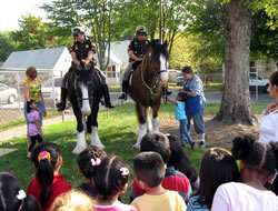 Police officers on their horses speaking to a group of Head Start students