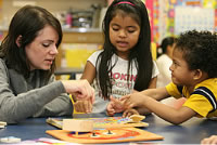 Photo of teacher working on a puzzle with two students.