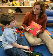 Photo of woman showing a book to a young boy